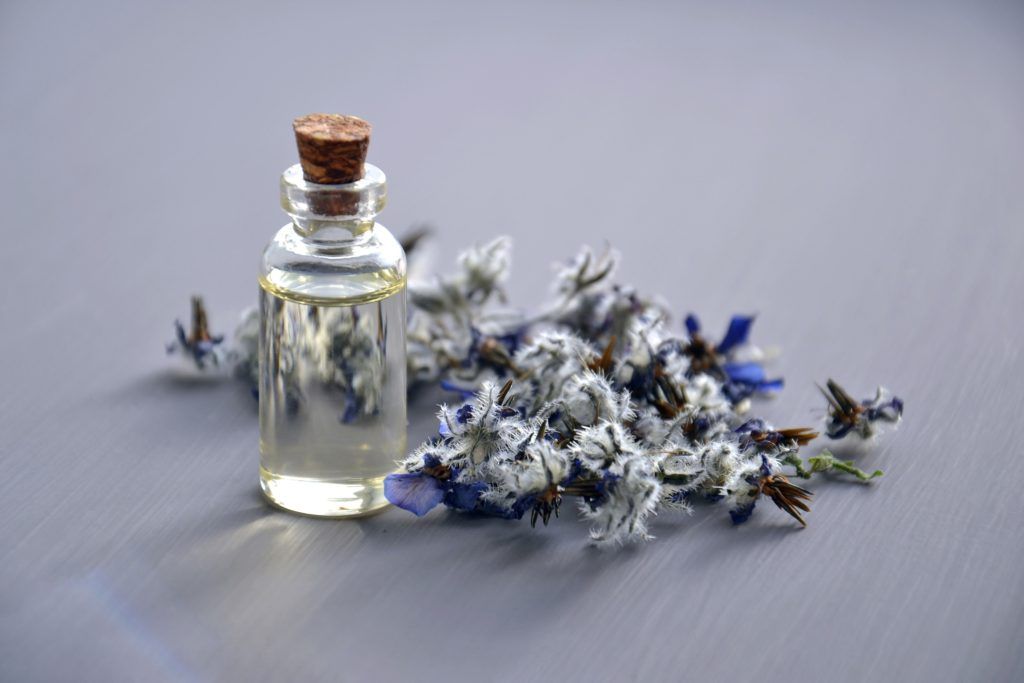 Aromatherapy bottle & flowers.  The best essential oils to balance hormones.