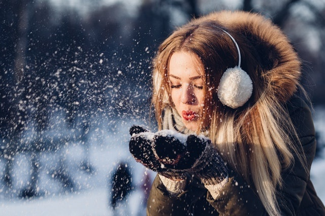 A pretty lady wrapped up warm, blowing snow from her hands.  The best essential oils to use through the winter.
