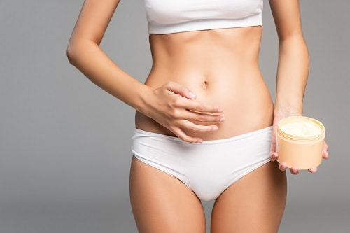 Lady applying cream to her abdomen.  How to heal scars with essential oils.