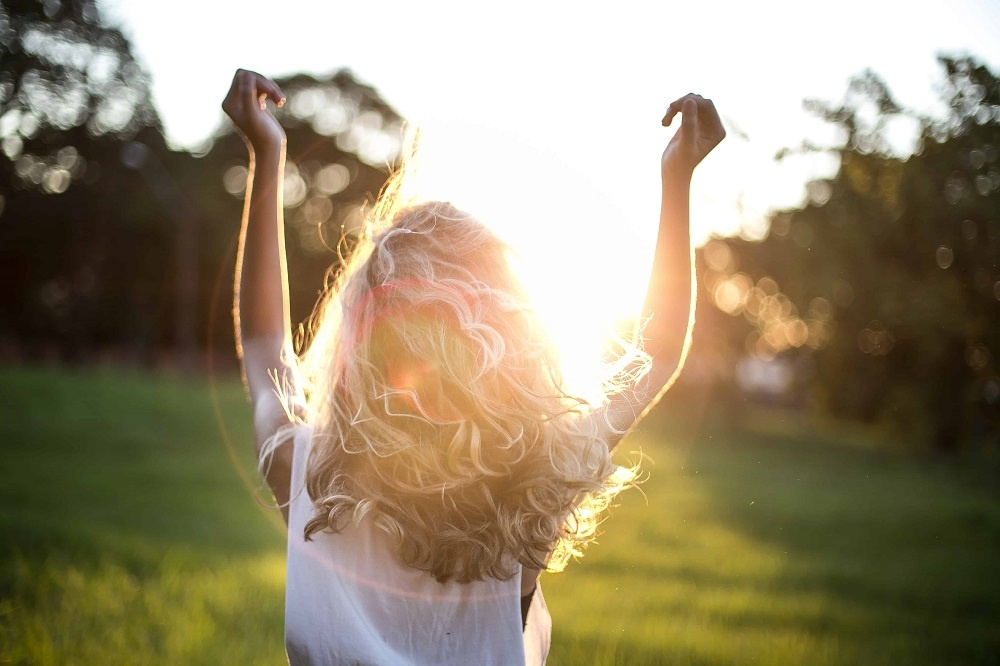 Lady facing away in the sunlight, arms up feeling joy.  Self-care -how to live the good life
