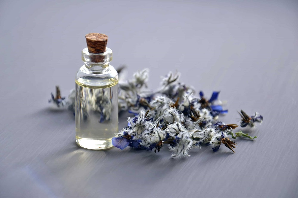 A small bottle of oil, laying next to some flowers.  The 10 best essential oils for dry skin and how to use them.