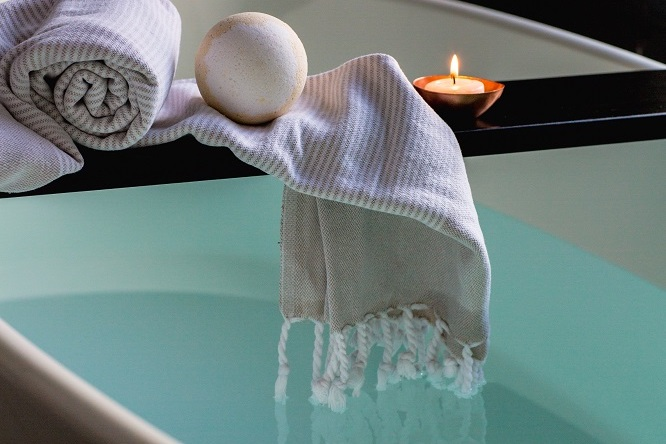 A towel draping over the side of a bath.  Using essential oils.