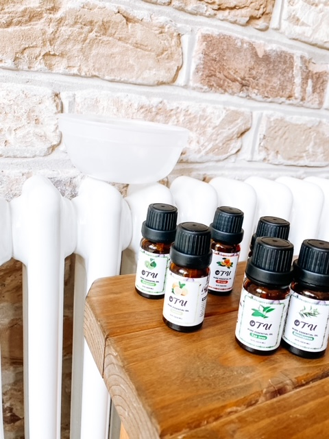 Essential oils on a stool next to radiator.  A small bowl is on the radiator.  How to burn essential oils without a diffuser.