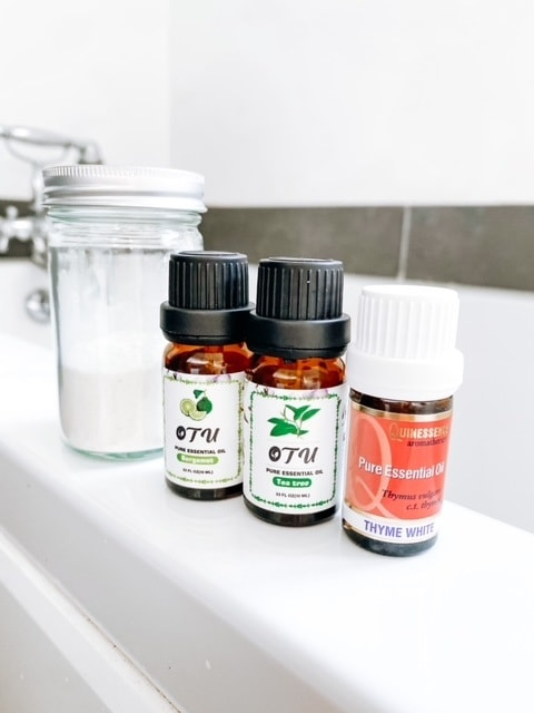 A jar of powder with small bottles of essential oils.  The best essential oils for athletes foot.