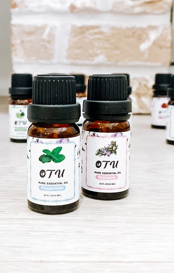 The best essential oils to help brain fog & improve concentration.   Peppermint & Rosemary essential oils on a shelf with other oils in the background.