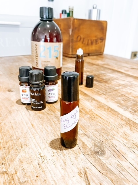 A roller applicator bottle on a table with several oils.  Essential oils to relieve under eye bags, puffiness & dark circles.