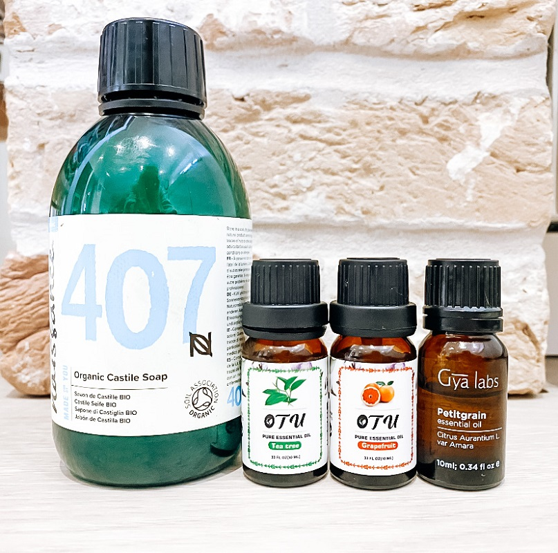 Organic castile soap, tea tree, grapefruit and petitgrain essential oils in front of a wall.  Natural, homemade face wash with essential oils.