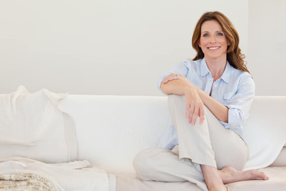 A lady sitting on a sofa smiling. Using essential oils