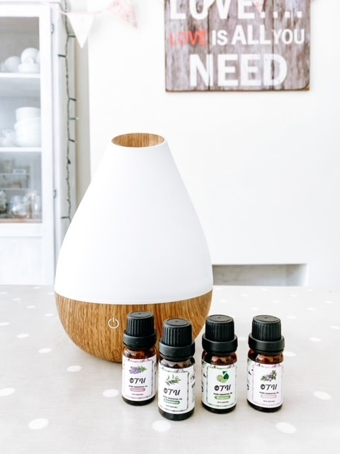 Essential oils on a spotty table cloth with a diffuser.  Essential oils to keep bugs away naturally