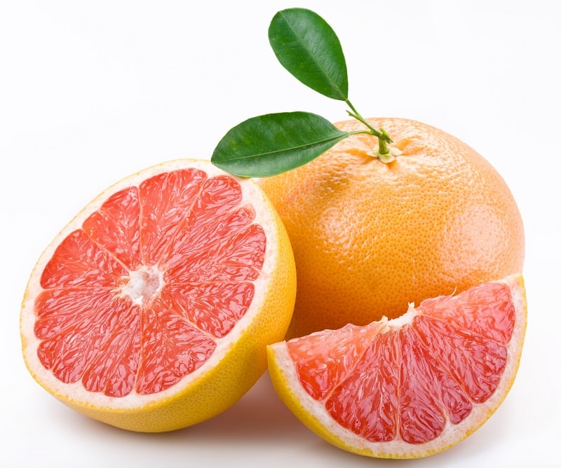 A whole grapefruit, next to a sliced grapefruit with bright pink, juicy flesh.  What does grapefruit essential oil blend well with.