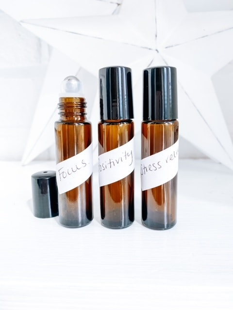3 roller bottles on a white shelf, with labels.  Easy roller ball recipes with essential oils